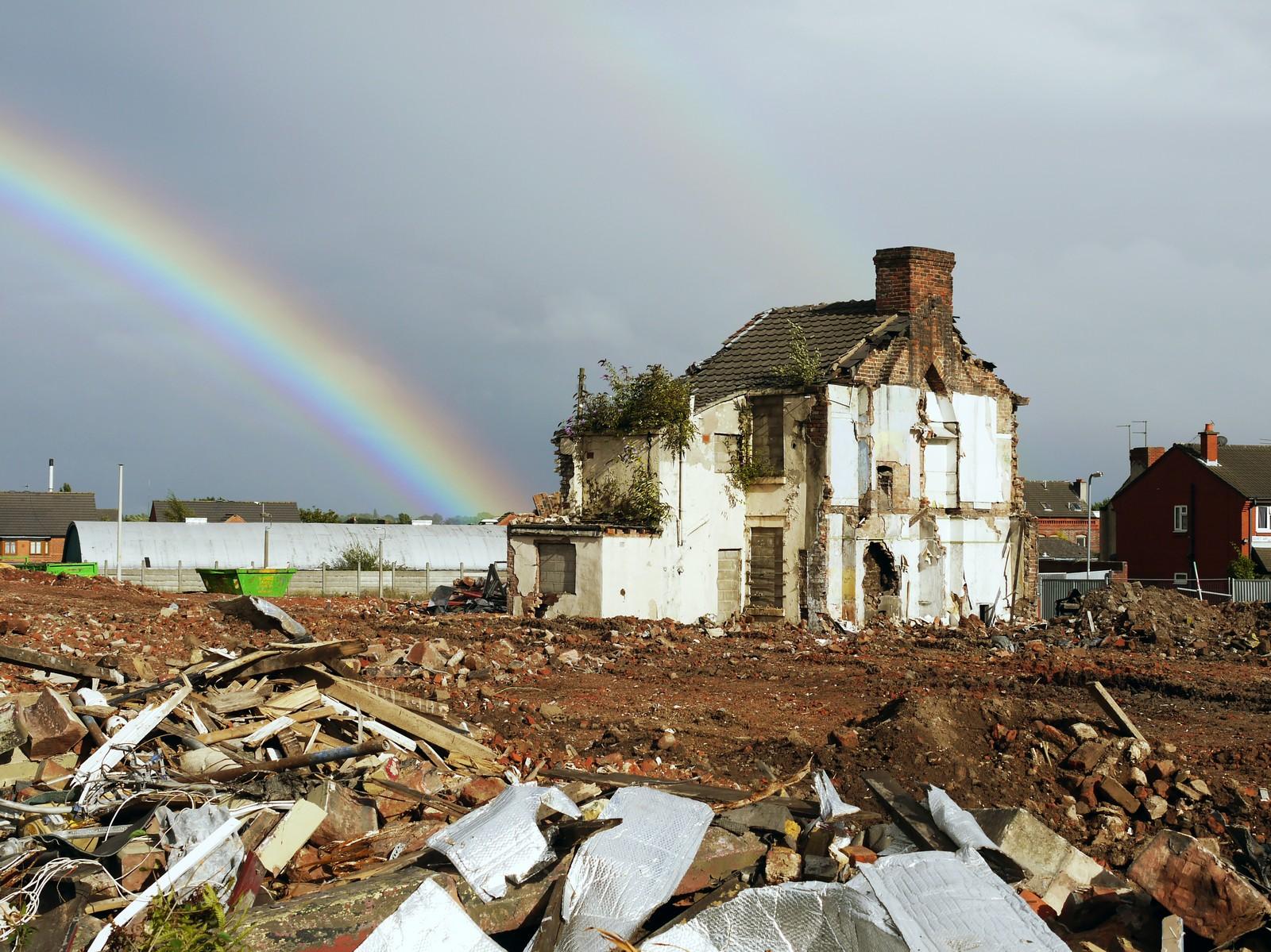 Run down house with a rainbow on the left