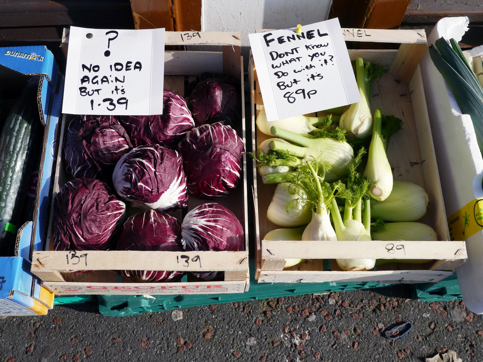 Two wooden crates with purple and green vegetables